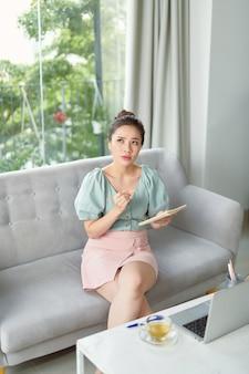 ノートブックに書き込み、ラップトップを使用して自宅で自己教育成熟した女性