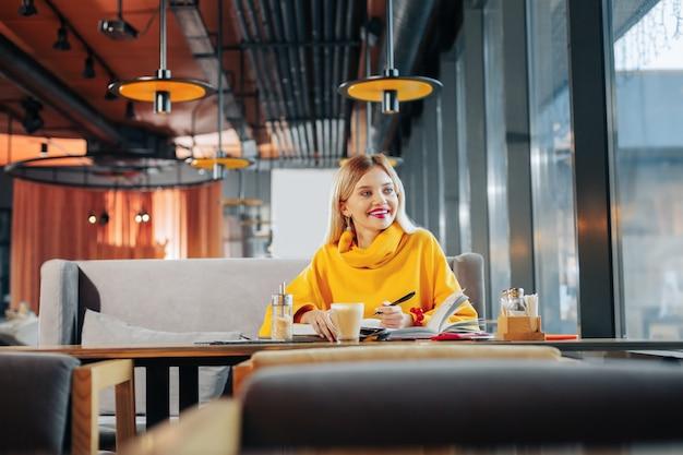 独学の時間。カフェテリアに座って独学の時間を楽しんでいる若い金髪の女性