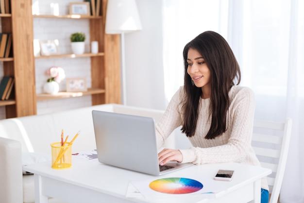 自営業。ノートパソコンで作業し、テーブルでポーズをとる魅力的な楽しい女性フリーランサー