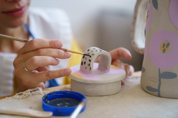 도자기 스튜디오의 마스터 클래스에서 점토 주전자를 위한 세라믹 컵을 장식하는 자영업 도예가 소녀