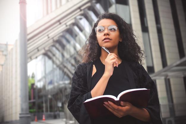 자영업 혼혈 여성 기업가가 공책에 쓰기 바쁘다