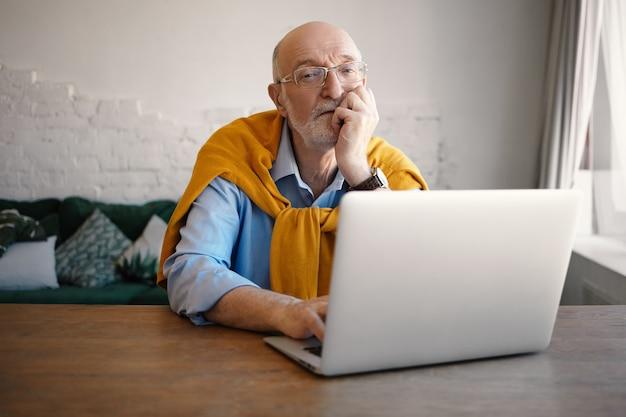 自営業の無精ひげを生やした老人がポータブルコンピュータでキーボード操作を行い、遠隔作業にワイヤレスインターネット接続を使用しています。オンラインコミュニケーションを楽しんでいる眼鏡の現代のシニア成熟した男性