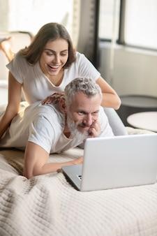 自己雇用。ベッドに横たわっている間、自宅でラップトップに取り組んでいるひげを生やした笑顔の男と近くの楽しい女性