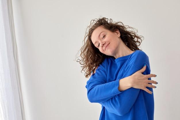 白い壁の背景に幸せな自信を持って若い女性の自己抱擁