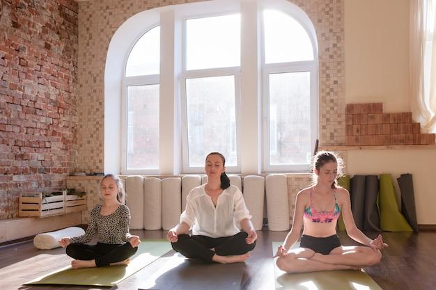 一緒に自己改善。女性の瞑想のクラス。集中力を考え、インストラクターと一緒にヨガスタジオで若い瞑想の女の子。 10代のスポーツ、ジムの背景、健康的なライフスタイル
