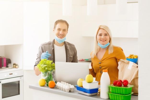 自己分離の概念。キッチンで紙袋を開梱し、流行の発生時に検疫の準備ができているカップル