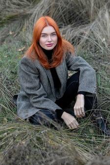 Самоизоляция на свежем воздухе. девушка, сидящая одна в зеленом лесу, наслаждается тишиной и красотой природы.