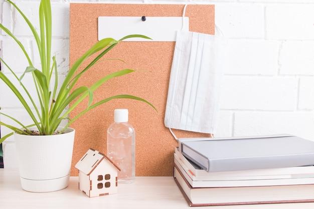 안면 마스크, 소독제, 코르크 보드, 꽃 및 책 더미가있는자가 격리 워크 스테이션, 테이블 위의 집 모델