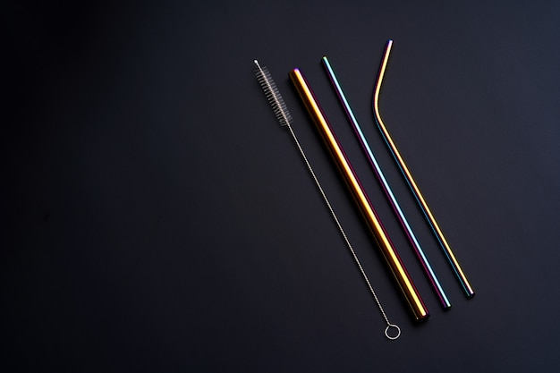 Self kit of reusable metal beverage straws of various diameters, colors and shapes with cleaning tool. on black background.