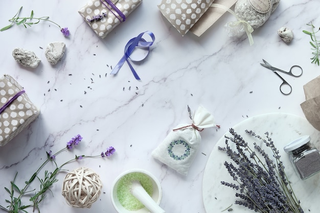 Self made lavender sachets, sugar scrub and aromatic herb infused bath salt. flat lay on white marble.