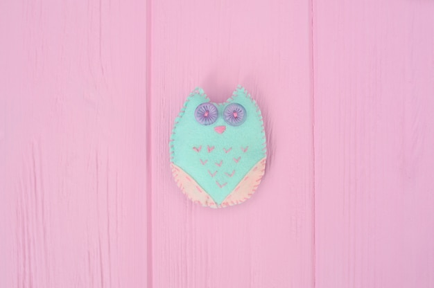 Self-made soft toy owl made of felt crafts on a pink wooden