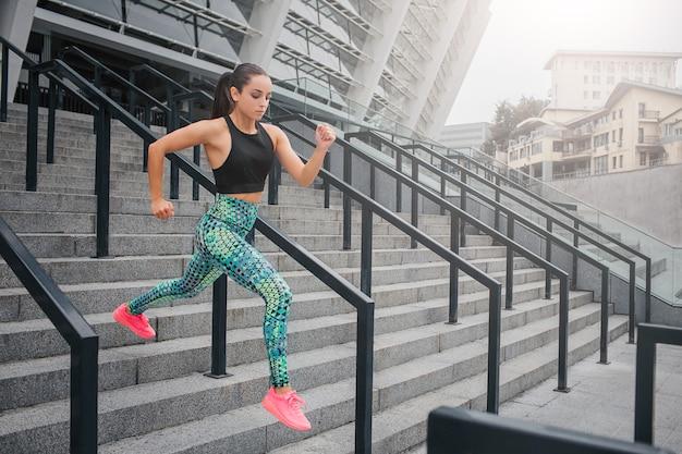 자기 의욕이 넘치고 집중된 젊은 여성은 매우 빨리 달린다. 그녀는 계단에서 그것을합니다. 모델이 아래를 내려다봅니다. 그녀는 아름다운 유니폼을 입고 있습니다. 여자는 거기에 혼자