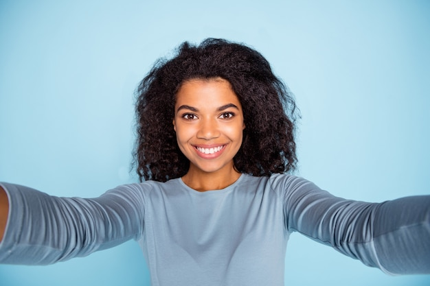 Self photo of cheerful positive beaming girlfriend smiling cheerfully taking selfie in blue sweater isolated pastel color background