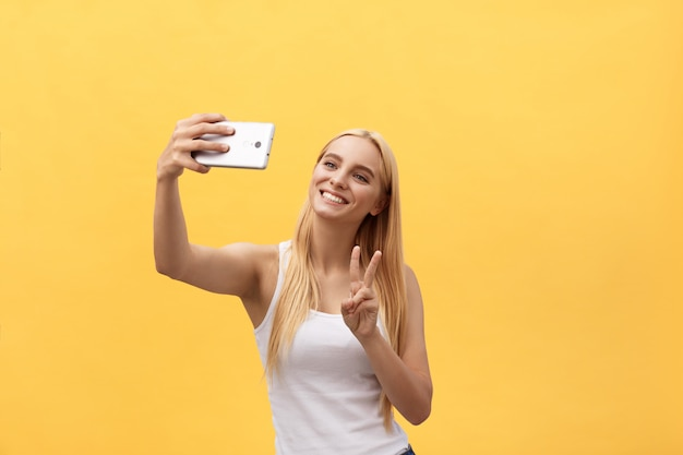 Self portrait of charming cheerful girl shooting selfie on front camera gesturing v-sign peace symbol