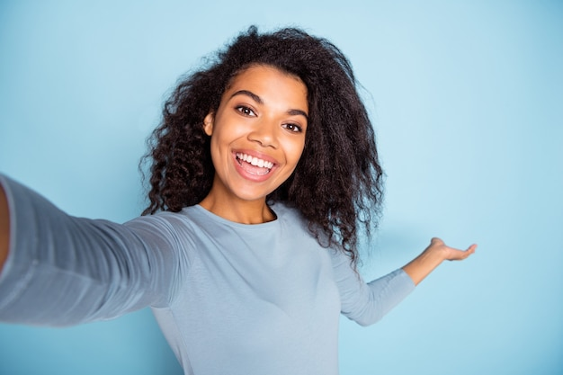 Self portrait of cheerful curly wavy positive cute nice pretty sweet girl welcoming you to come to empty space showing while traveling isolated pastel color background