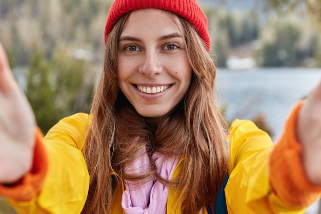 Self portrait of happy girl with european appearance, charming smile, wears red hat and yellow anorak, explores world while wanders