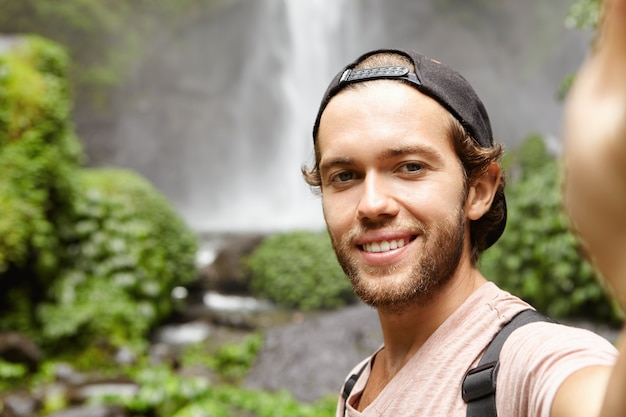 Self-portrait of happy hiker in baseball cap taking selfie while standing against waterfall in green exotic woods. young tourist trekking in rainforest during his holidays