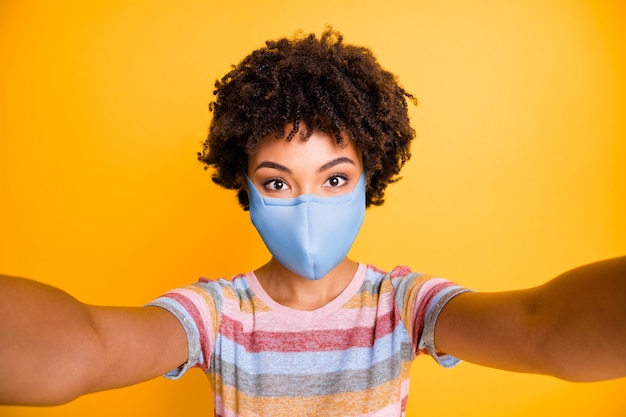 Self-portrait of her she nice focused attractive wavy-haired girl wearing safety textile reusable mask stop wuhan mers cov influenza flue isolated bright vivid shine vibrant yellow color background