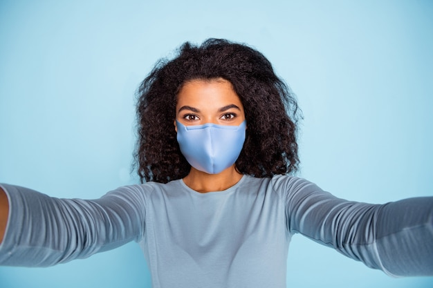 Self-portrait of her she nice lovely attractive girl wearing reusable cotton textile mask stop pandemia respiratory wuhan mers cov influenza flue prevention isolated blue pastel color background
