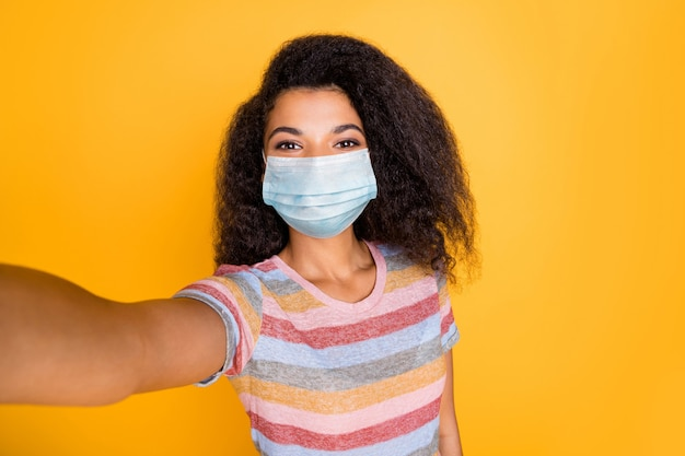 Self-portrait of her she pretty wavy-haired girl wearing gauze surgical safety mask respirator spending summer sickness disease prevention isolated bright vivid shine vibrant yellow color background
