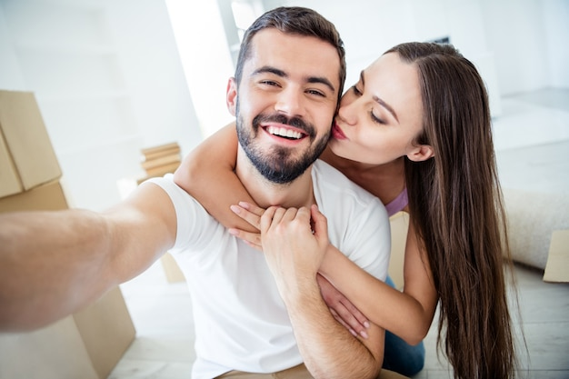 Self-portrait of his he her she nice attractive cheerful cheery dreamy married spouses embracing kissing rent loan purchase accommodation at flat light white interior house indoors