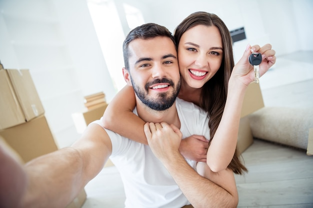 Self-portrait of his he her she nice attractive cheerful tender married spouses embracing holding in hand key rent loan lease purchase accommodation place at flat light white interior house