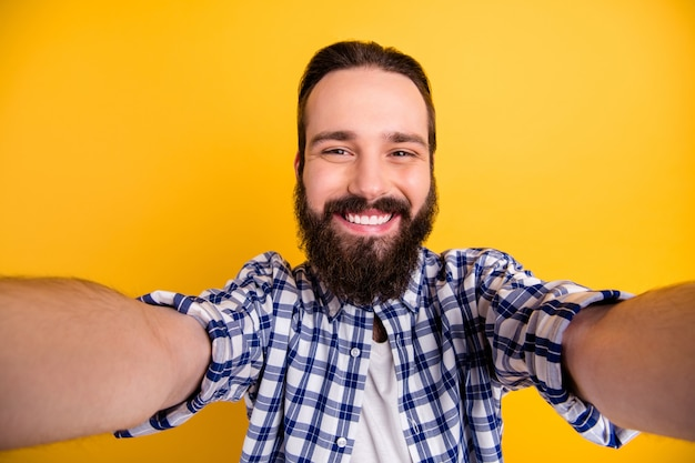 Self-portrait of his he nice attractive cheerful cheery bearded guy wearing checked shirt