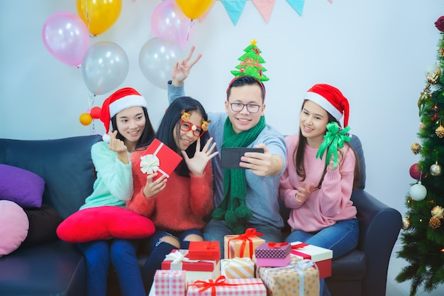 Self portrait of mixed race friends : asian young smiling bearded men and beautiful women in red christmas hat posing, celebrating new year and holidays concept