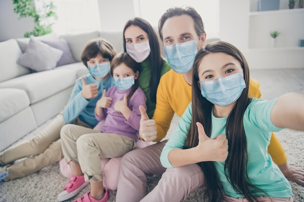 Self-portrait of nice attractive big full family pre-teen kids mom dad showing thumbup spending time holiday day mers cov preventive measures stop infection at house apartment living-room