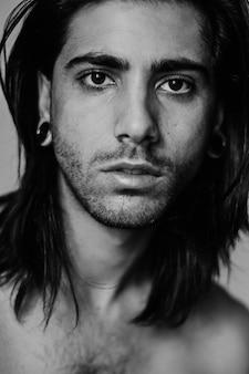 Автопортрет молодого человека с длинными волосами и расширителем слуха в черно-белом