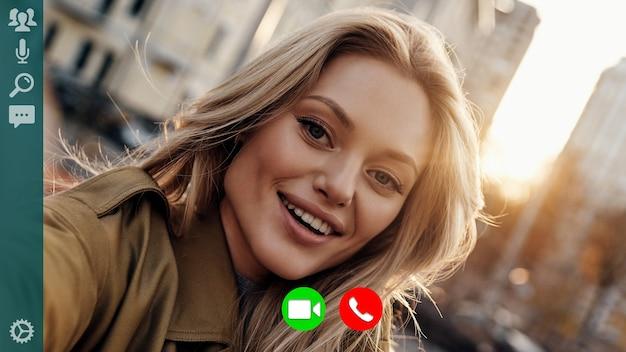 Автопортрет привлекательной молодой женщины, улыбающейся и смотрящей в камеру во время видеозвонка на открытом воздухе
