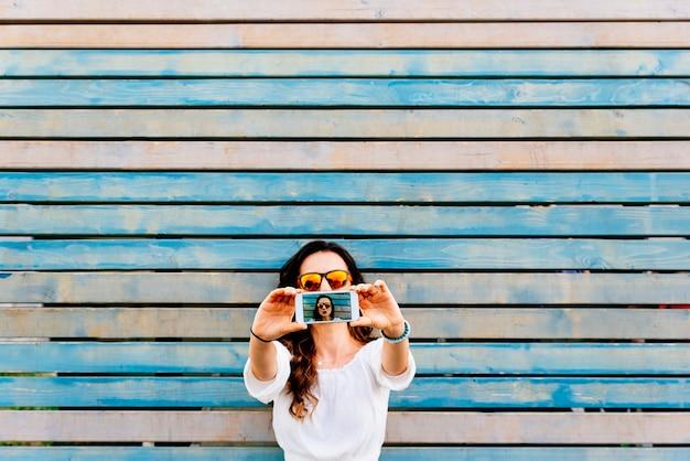 モバイルで美しい若い女性の自画像。セルフィーコンセプト。