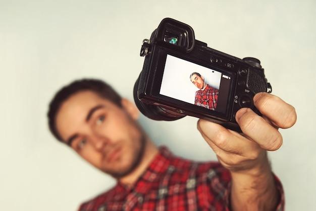 Автопортрет веселого бородатого блогера в рубашке, снимающего селфи, снимающего видео для своего блога на желтом фоне. красивый молодой человек фотографирует себя. хипстер с камерой в руке