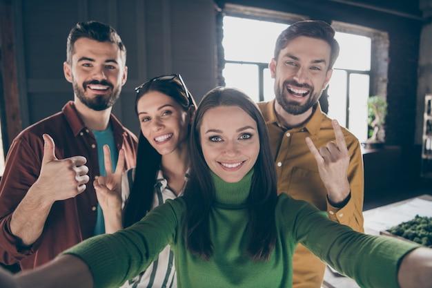 Автопортрет четырех хороших привлекательных радостных позитивных жизнерадостных веселых менеджеров, показывающих большой палец вверх рог, весело проводящих время