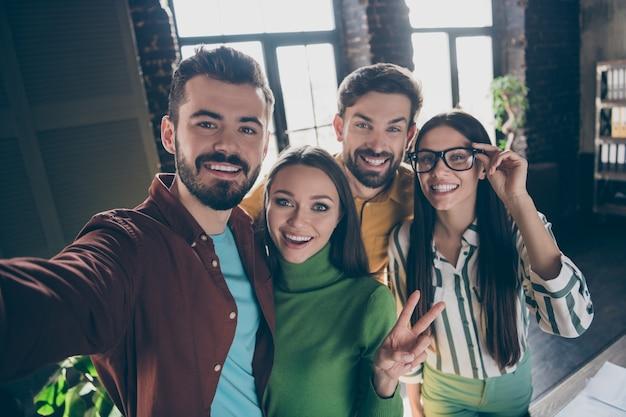Автопортрет четырех хороших привлекательных радостных позитивных веселых веселых профессиональных людей, исполнительных менеджеров, показывающих v-знак, весело проводящих время