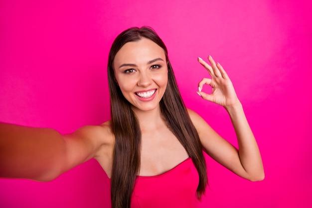 彼女の自画像彼女の見栄えの良い魅力的な素敵なゴージャスなコンテンツ陽気な陽気な嬉しい長髪の女の子は、明るい鮮やかな輝きの鮮やかなピンクのフクシア色の背景に分離されたokサインを示しています