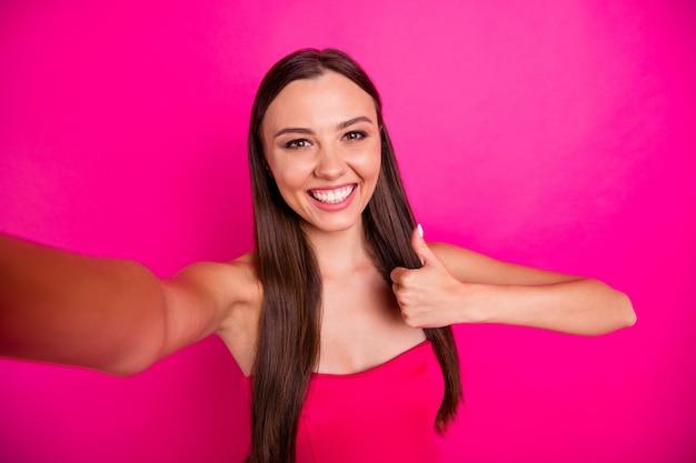 彼女の自画像彼女の見栄えの良い魅力的な素敵なゴージャスなコンテンツ陽気な陽気な長髪の女の子は、明るい鮮やかな輝きの鮮やかなピンクのフクシア色の背景に分離されたサムアップ広告を示しています