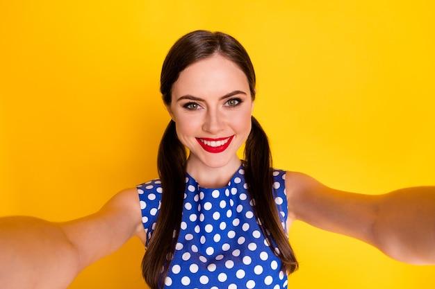彼女の自画像彼女の見栄えの良い魅力的なかなり素敵な魅力的な陽気な陽気な女の子は、明るい鮮やかな輝きの鮮やかな黄色の背景に分離された青いモダンなテキスタイルブラウスを着ています