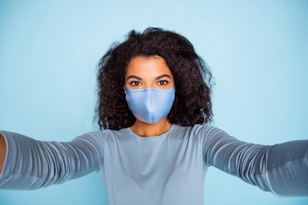 Автопортрет ее милая милая привлекательная девушка в многоразовой хлопковой текстильной маске остановить пандемию респираторных ухань mers cov профилактика гриппа изолированный синий пастельный цвет фона