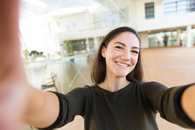 Автопортрет радостная красивая женщина, держащая смартфон