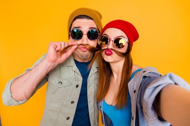 밝고 선명한 노란색 배경에서 격리된 재미있는 가짜 콧수염을 만드는 주말을 보내는 멋지고 유치하고 유머러스한 쾌활한 커플의 자화상