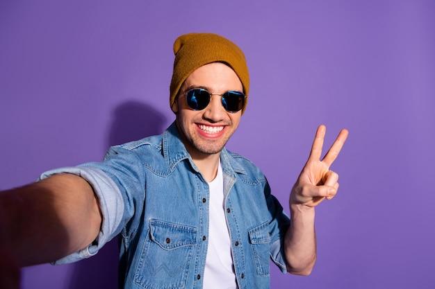 Автопортрет модного веселого доброго стильного привлекательного красивого парня, делающего селфи, показывающего вам, зубасто улыбающегося v-образного знака на ярком фиолетовом цветном фоне