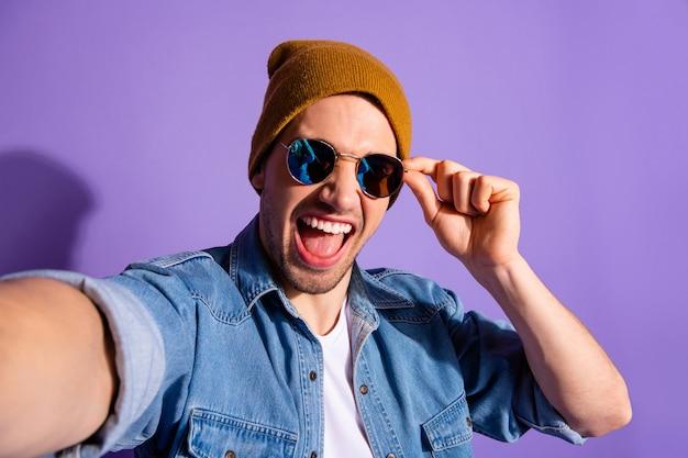 トレンディでスタイリッシュで魅力的なハンサムなブロガーの自画像は、鮮やかな色の紫色の背景の上に孤立した自撮り写真を撮って眼鏡をまっすぐに叫んで聴衆に影響を与えています