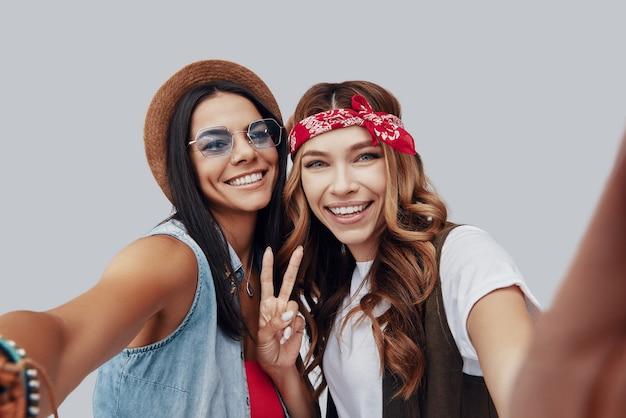 회색 배경에 서있는 동안 카메라를보고 웃고 두 매력적인 세련된 젊은 여성의 자기 초상화