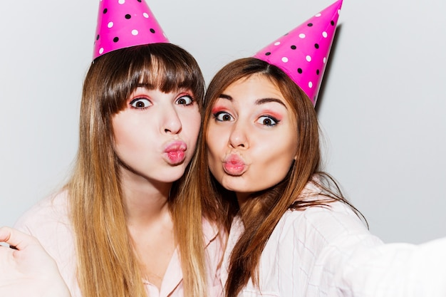 ピンクの紙の誕生日帽子の2人の女性のセルフポートレート。ピンクのパジャマを着てキスをする友達。遊び心のある気分。