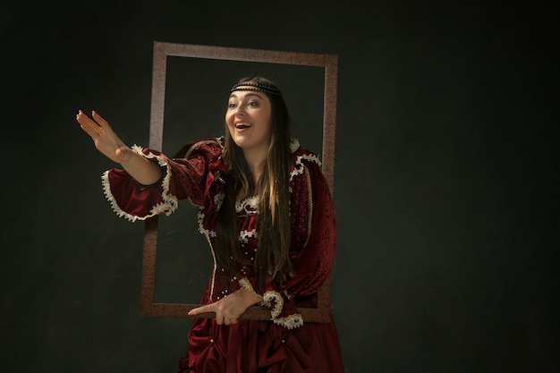 Self portrait. portrait of medieval young woman in red vintage clothing standing on dark background. female model as a duchess, royal person. concept of comparison of eras, modern, fashion, beauty.