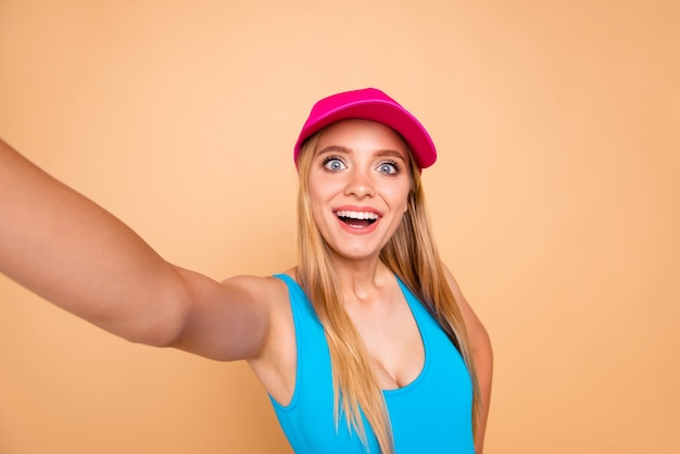 Self-portrait of young cute girl wearing bright pink cap isolated on beige