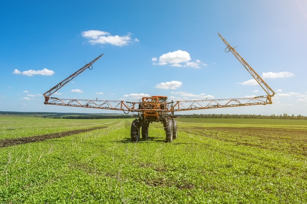 Self-propelled sprayer works on a field under a blue sky with clouds