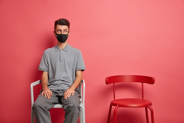 Self quarantine concept. sad lonely man wears protective mask stays at home during isolation being depressed because of outbreak situation sits near empty chair