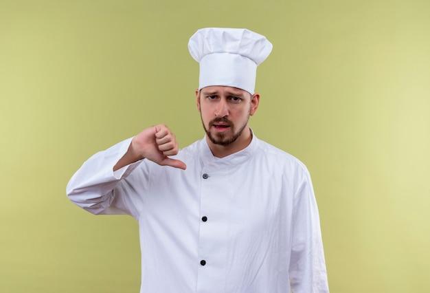自己満足のプロの男性シェフが白い制服を着て調理し、greeの背景の上に立っている自分を指している帽子を調理します。